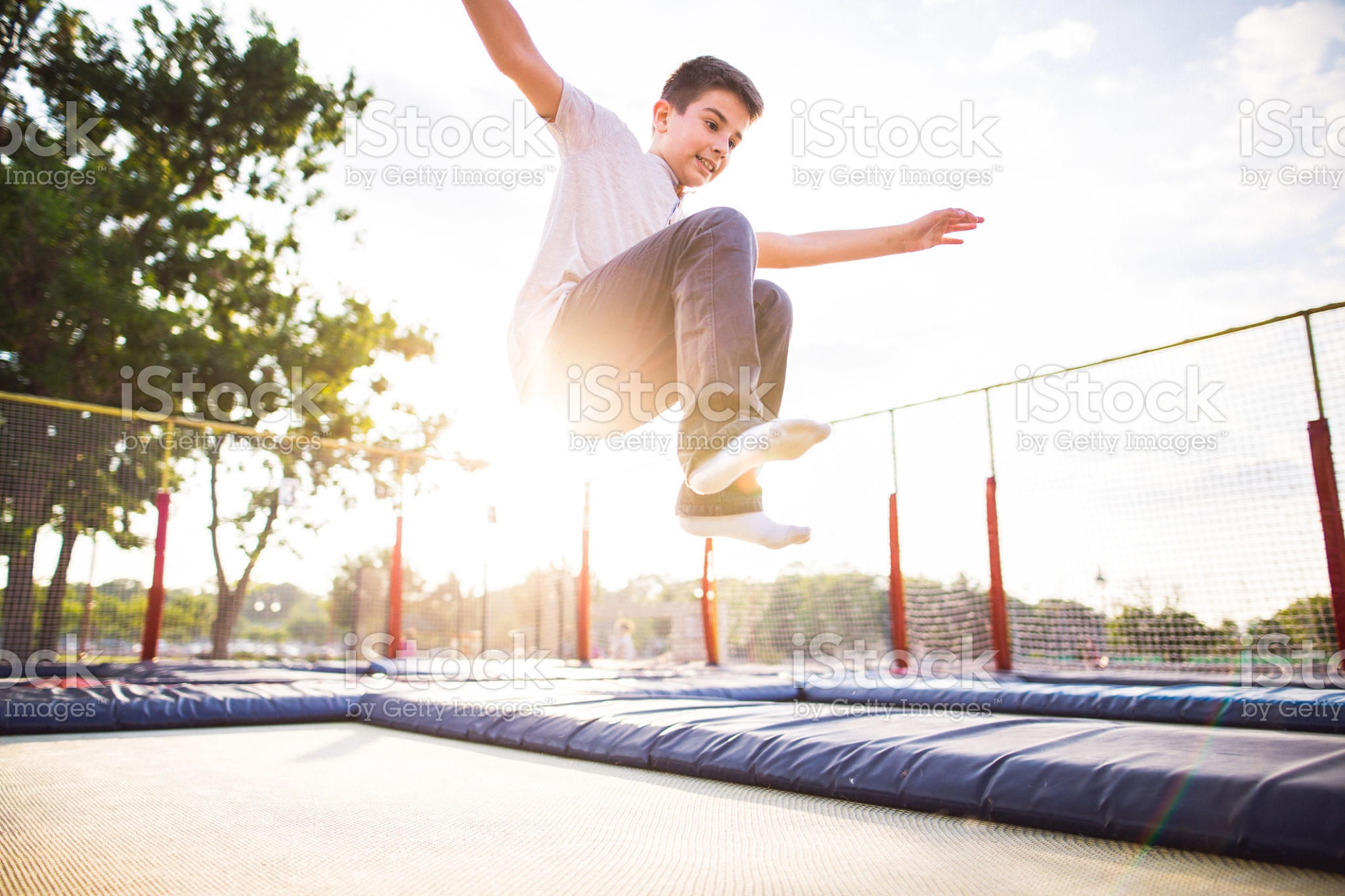 Photo of  boy jumping open arms on the trampoline in the park
